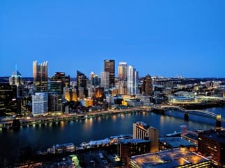 This is a birds eye view photo of the city of Pittsburgh after the sun has set.